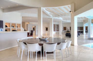 Vista de la cocina bar y su mesa en la sala principal de la Villa del Mar, frente al mar